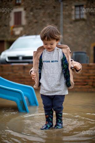 大きな水たまりで遊ぶハーフの幼児の写真素材 [FYI03822998]