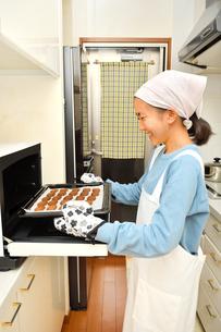 キッチンでクッキーを焼く女の子の写真素材 [FYI03823014]