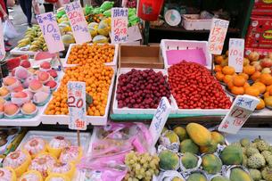 香港・旺角(モンコック/Mong Kok)の市場で売られる、ミカン、ナツメヤシ、モモ、パパイアの果物。日本、タイ、米国など、世界中から輸入されているの写真素材 [FYI03823178]