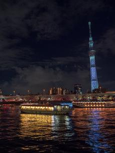 ライトアップされたスカイツリーと、花見を楽しむ隅田川の屋形船の写真素材 [FYI03823942]