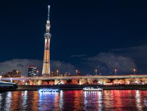 ライトアップされたスカイツリーと、花見を楽しむ隅田川の屋形船の写真素材 [FYI03823947]