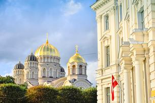 ラトビア・首都リガにある救世主生誕大聖堂とラトビアの国旗が飾られた建物・大聖堂はロシア帝国時代の19世紀後半に建設されたネオ・ビザンチン様式の壮麗な建物の写真素材 [FYI03824450]