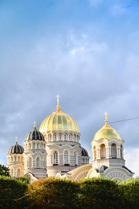 ラトビア・首都リガにある救世主生誕大聖堂とラトビアの国旗が飾られた建物・大聖堂はロシア帝国時代の19世紀後半に建設されたネオ・ビザンチン様式の壮麗な建物の写真素材 [FYI03824453]