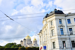 ラトビア・首都リガにある救世主生誕大聖堂とラトビアの国旗が飾られた建物・大聖堂はロシア帝国時代の19世紀後半に建設されたネオ・ビザンチン様式の壮麗な建物の写真素材 [FYI03827253]