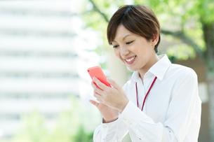 スマートフォンを見て笑うOLの写真素材 [FYI03827288]