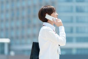 携帯電話で話しながらビジネス街を歩くOLの写真素材 [FYI03827313]