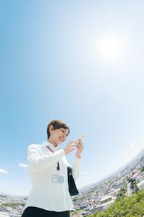 住宅街でスマートフォンを見るOLの写真素材 [FYI03827323]