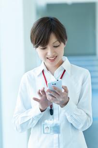 スマートフォンを見ながら微笑むOLの写真素材 [FYI03827394]