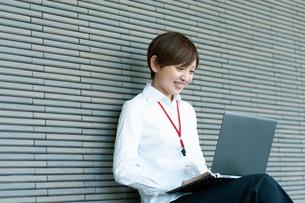ベンチに座ってノートPCを操作するOLの写真素材 [FYI03827400]