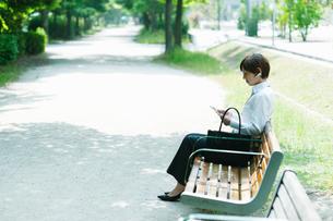 ベンチに座ってタブレットを操作するOLの写真素材 [FYI03827402]