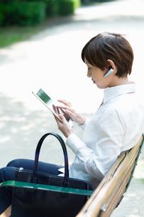 ベンチに座ってタブレットを操作するOLの写真素材 [FYI03827403]