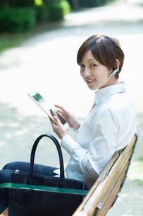 ベンチに座ってタブレットを操作するOLの写真素材 [FYI03827404]