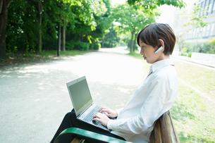 ベンチに座ってノートPCを操作するOLの写真素材 [FYI03827405]