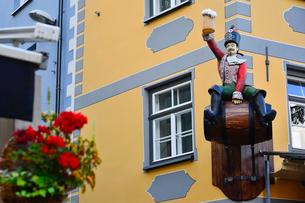 ラトビア歴史地区世界遺産リガ旧市街の建物に飾られた樽に乗ってビールのジョッキを持つ男性の像の写真素材 [FYI03827980]