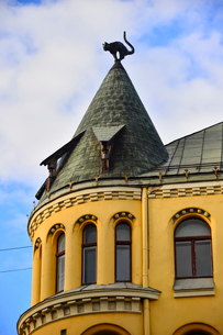 ラトビア歴史地区世界遺産リガ旧市街のアールヌーヴォー建築の貴重な建物で猫の家と言われている・かつての住人のラトビア人がギルド(ドイツ人のみ入会が許されていた商工業者の会)の入会拒否されギルド会館にお尻を向けた猫の像を屋根に付けたが後には入会できて現在はギルド会館の方に向きを変えているの写真素材 [FYI03827981]