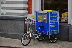 ラトビア・首都リガ歴史地区の道路わきに置かれた三輪車に乗せられた旧市街のツアー案内箱の写真素材 [FYI03828028]