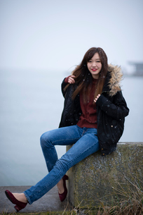 岸壁に座る女性の写真素材 [FYI03828091]