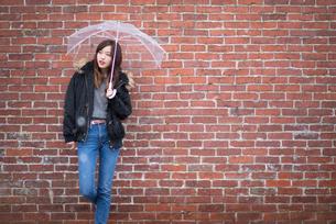 レンガ壁の前で傘をさす女性の写真素材 [FYI03828104]