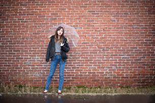 レンガ壁の前で傘をさす女性の写真素材 [FYI03828105]