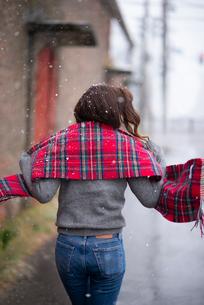 雪の中を歩く女性の後ろ姿の写真素材 [FYI03828112]