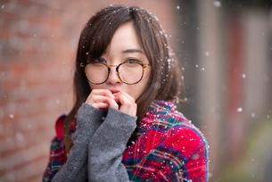 雪の中で手を合わせる女性の写真素材 [FYI03828118]