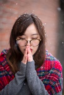 雪の中で手を合わせる女性の写真素材 [FYI03828119]