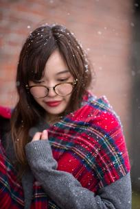 雪の中でストールを巻く女性の写真素材 [FYI03828120]