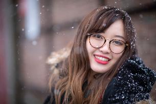 雪の中で微笑む女性の写真素材 [FYI03828123]