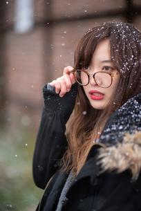 雪の中で眼鏡を外す女性の写真素材 [FYI03828124]