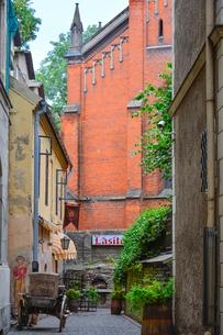 ラトビア・首都リガ歴史地区の敷石の道路に置かれた木製の荷車とネオゴシック様式の英国教会の尖塔のある光景の写真素材 [FYI03828646]