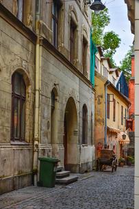 ラトビア・首都リガ歴史地区の敷石の道路に置かれた木製の荷車と中世風の建物の写真素材 [FYI03828762]