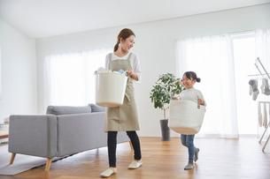 リビングルームで洗濯物を干す親子の写真素材 [FYI03828882]