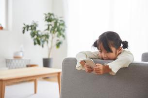 リビングのソファでスマートフォンを触っている子供の写真素材 [FYI03828894]