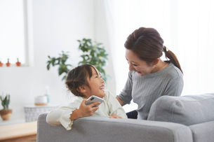 リビングのソファでスマートフォンを触っている親子の写真素材 [FYI03828896]