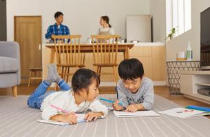 リビングでお絵かきをする子供とキッチンに立つ両親の写真素材 [FYI03828905]