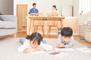 リビングでお絵かきをする子供とキッチンに立つ両親の写真素材 [FYI03828907]