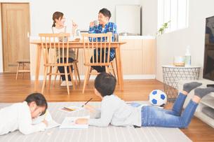 リビングでお絵かきをする子供とダイニングで会話をする両親の写真素材 [FYI03828908]