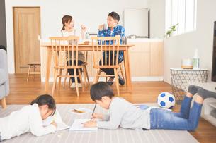 リビングでお絵かきをする子供とダイニングで会話をする両親の写真素材 [FYI03828909]