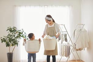 リビングルームで洗濯物を干す親子の写真素材 [FYI03828927]