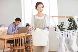 洗濯をする母とパソコンを見ている父と子の写真素材 [FYI03828928]