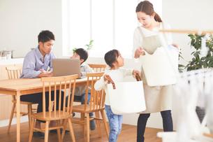 洗濯をする母とパソコンを見ている父と子の写真素材 [FYI03828929]