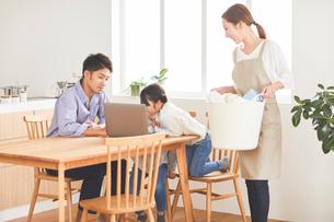 洗濯をする母とパソコンを見ている父と子の写真素材 [FYI03828931]