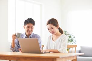 ダイニングでパソコンを見ている夫婦の写真素材 [FYI03828934]