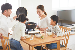 鍋料理を食べる家族の写真素材 [FYI03828943]