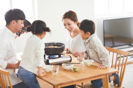 鍋料理を食べる家族の写真素材 [FYI03828945]