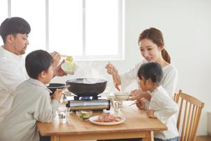 鍋料理を食べる家族の写真素材 [FYI03828952]