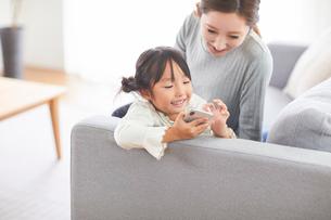 リビングのソファでスマートフォンを触っている子供とお母さんの写真素材 [FYI03828963]