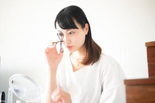 ビューラーでまつ毛をカールしている女性の写真素材 [FYI03829053]