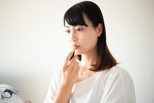 口紅を塗っている女性の写真素材 [FYI03829056]
