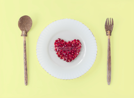 白い皿に盛り付けられたハート型のザクロの実とスプーンとフォークの写真素材 [FYI03829077]